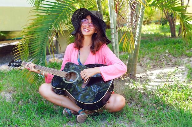 Ritratto di moda all'aperto di donna hippie abbastanza sorridente felice che si siede sull'erba e che tiene la chitarra acustica. paese tropicale caldo, sfondo verde. vestito estivo con cappello e occhiali da sole rosa. Foto Gratuite