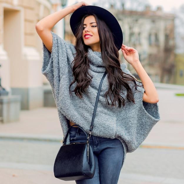 トレンディな秋の服、黒い帽子、灰色のセーター、革のバッグを身に着けているグラマー官能的な若いスタイリッシュな女性のアウトドアファッションの肖像画。真っ赤な唇。旧市街の背景。 無料写真
