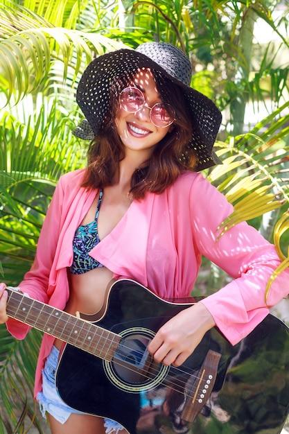 草に座って、アコースティックギターを持って幸せなかなり笑顔のヒッピー女のアウトドアファッションの肖像画。熱帯の暑い国、緑の背景。帽子とピンクのサングラスの夏の服装。 無料写真