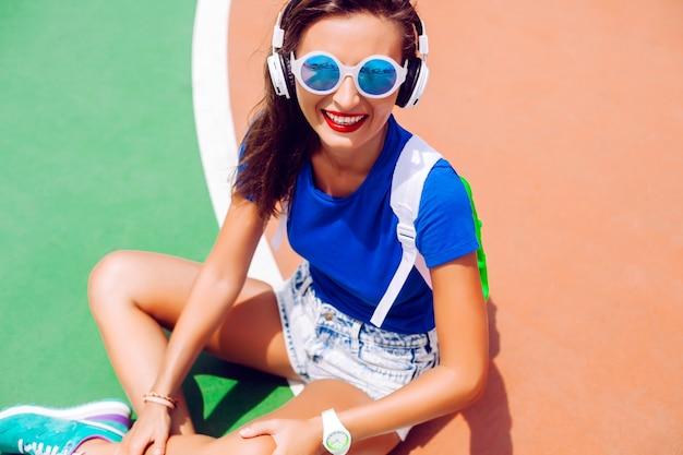Открытый модный портрет хипстерской девушки, позирующей на спортивной площадке в ярком летнем наряде, слушающей музыку и носящей стильный спортивный рюкзак и солнцезащитные очки. Бесплатные Фотографии