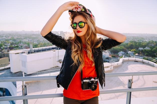 ヴィンテージのレトロなカメラを保持し、明るい盗品の帽子、流行のサングラスと革のジャケットを身に着けているスタイリッシュな写真家の女の子の屋外ファッションの肖像画、屋根からの街の素晴らしい景色 無料写真