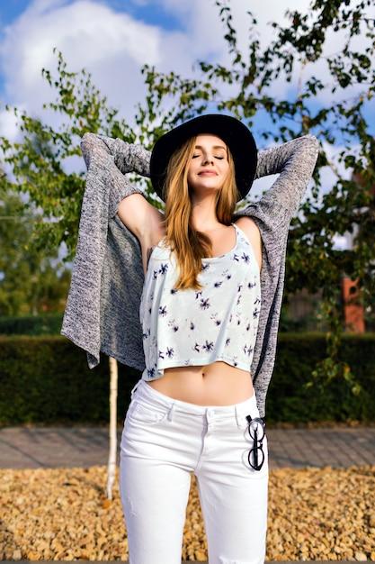 Открытый модный портрет стильной красивой молодой женщины, одетой в богемный наряд, винтажной шляпе, с длинными светлыми волосами, наслаждающейся свободным солнечным осенним днем и хорошей погодой, расслабляющей, расслабляющей, радостной, отпускной. Бесплатные Фотографии