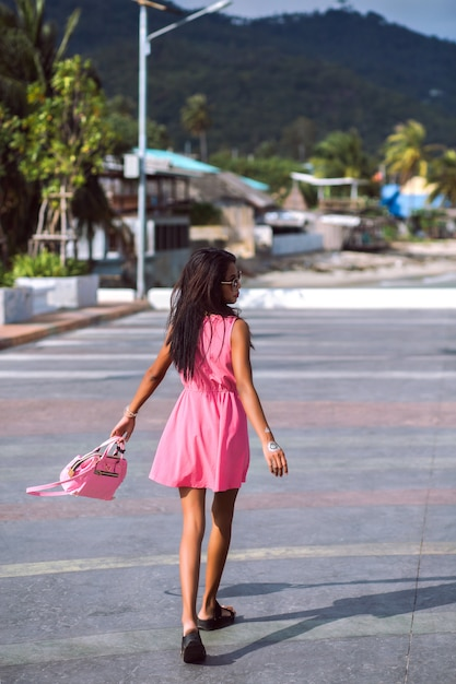 Ritratto di moda all'aperto di donna tailandese asiatica piuttosto sottile in posa per strada, indossando mini abito rosa, sandali, occhiali da sole e borsa abbinata ai colori, umore di viaggio. Foto Gratuite
