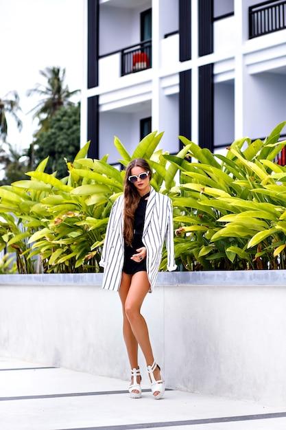 Ritratto di moda all'aperto di giovane donna castana alla moda che posa vicino a palme e indossa un vestito bianco e nero alla moda moderno Foto Gratuite