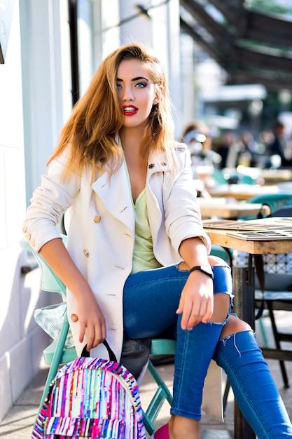 Ritratto di moda all'aperto di giovane donna splendida alla moda, che indossa jeans e cappotto elegante, trucco luminoso glamour, posa sulla terrazza del caffè della città, clone itinerante, giornata di sole. Foto Gratuite