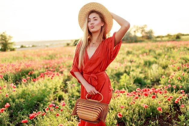 暖かい夏の夜の素晴らしいケシ畑を歩きながらポーズ美しいブロンドの女性の屋外のファッショナブルな肖像画。麦わら帽子、流行のバッグ、赤いドレスを着ています。 無料写真