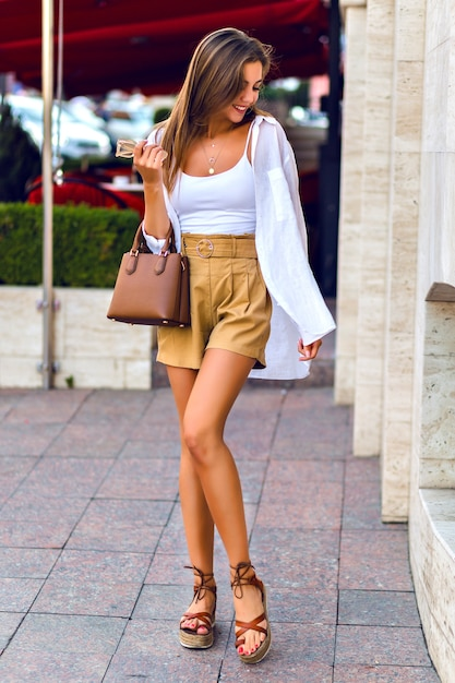Outdoor full length portrait of stunning slim tanned brunette model wearing linen beige shorts, caramel leather luxury bag, white shirt and gold accessories, walking at paris streets. Free Photo