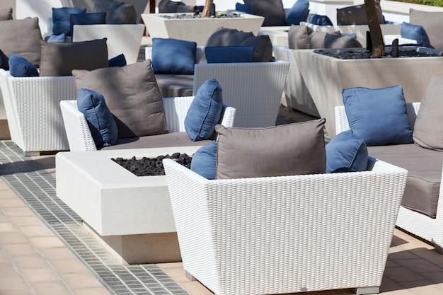屋外用家具籐のアームチェアとテラスのテーブル Premium写真