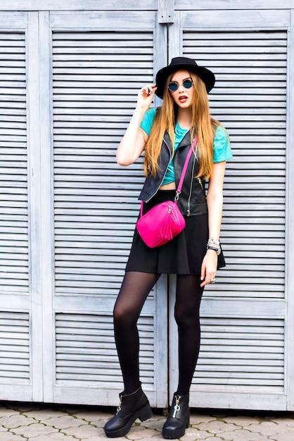 Ritratto di moda grunge all'aperto di donna bionda alla moda hipster, emozioni positive felici, in posa sul manzo, look elegante e luminoso, occhiali da sole, cappello, giacca di pelle e borsa a tracolla. Foto Gratuite