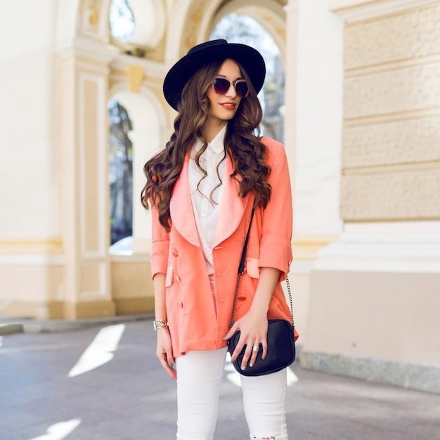 Outdoor hight fashion portrait of stylish casual woman in black hat, pink suit, white blouse posing on old street Free Photo