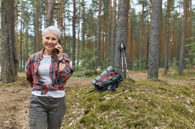 森の中を歩いて、電話で会話し、笑顔で、バックパックとバックグラウンドで木の下でマットを寝ているアクティブウェアでエネルギッシュな引退した女性の屋外の画像。人、旅行、テクノロジー 無料写真