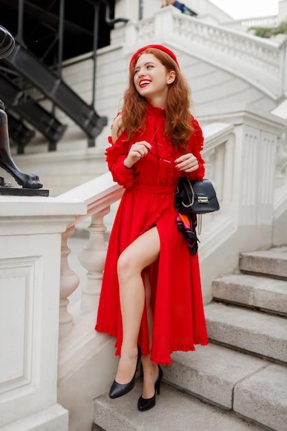 赤いベレー帽と美しいヨーロッパの都市の橋の近くの階段に立っているドレスでゴージャスな生姜女性の屋外画像。 無料写真