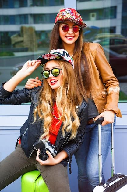 空港の近くで荷物を持って歩き、快適で明るくスタイリッシュな服を着て、旅行と新しい感情の準備ができている2人の親友の女の子のアウトドアライフスタイルの明るい肖像画 無料写真