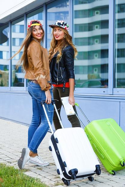 空港近くの荷物を持って歩く2人の親友の女の子のアウトドアライフスタイル明るい肖像画 無料写真