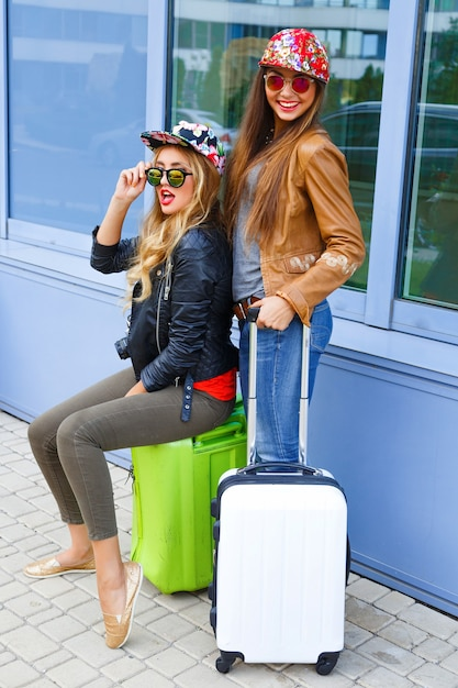 Ritratto luminoso di stile di vita all'aperto delle ragazze di due migliori amici che camminano con i loro bagagli vicino all'aeroporto, indossando abiti eleganti luminosi comodi, pronti per il viaggio e nuove emozioni Foto Gratuite
