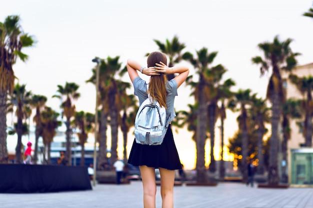 Открытый модный портрет молодой хипстерской женщины, идущей в барселоне, путешествие с рюкзаком, стильный повседневный наряд, вечерний закат, пальмы, студент, светлая прическа, счастливое время, тонированные цвета. Бесплатные Фотографии