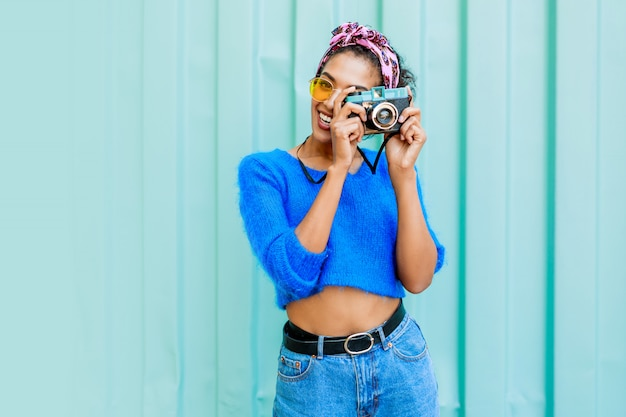 Outdoor lifestyle  image of fashionable  black woman in bright wool sweater and colorful  headband on hairs Free Photo