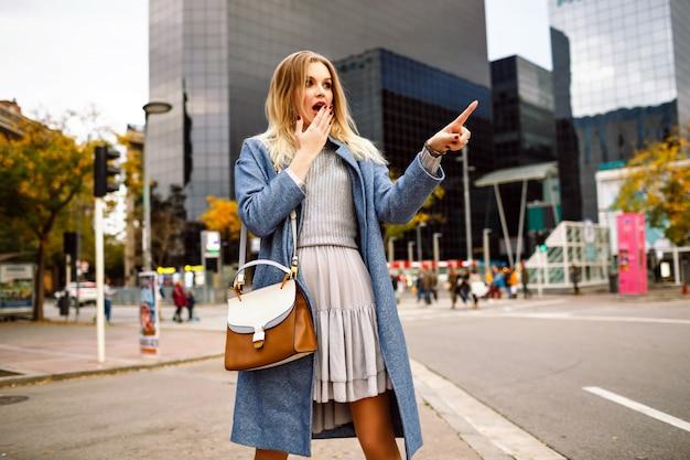 金髪のかなり若い実業家、モダンな建物エリアを歩いて、青いコートとフェミニンなグレーのドレスを着て、彼女の指で何かを見せて驚いた怖い感情のアウトドアライフスタイルの肖像画。 無料写真