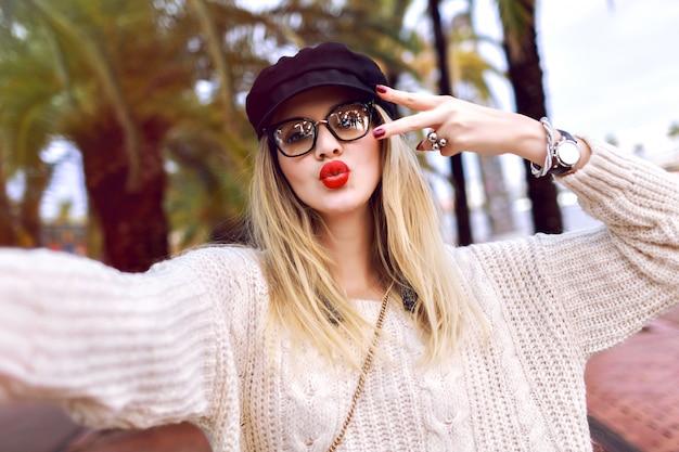 手のひら、秋の春の時間の前に通りでselfieを作る幸せな若いスタイリッシュな女性のアウトドアライフスタイルの肖像画、スタイリッシュなセーター、メガネ、帽子を身に着けているキスを送信、気分を旅行します。 無料写真