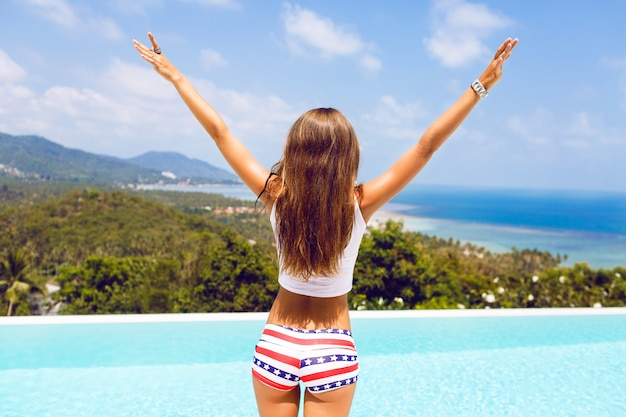 Открытый образ жизни портрет женщины с идеальным телом в сексуальных шортах поднял руки вверх и наслаждается своей свободой на удивительном тропическом острове. прекрасный вид на океан и горы Бесплатные Фотографии