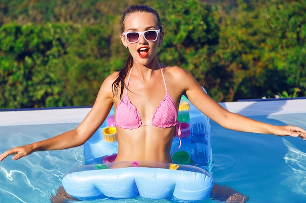 Outdoor lifestyle portrait of pretty sexy woman on vacation , wearing bright bikini and sunglasses, relax and having fun at pool party Free Photo