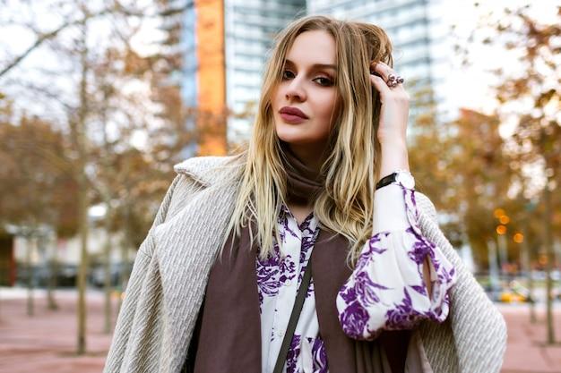 Открытый образ жизни положительный портрет красивой блондинки, улыбающейся в конце, наслаждается временем, гламурным элегантным нарядом, ношением платья и пальто, теплыми цветами, весенне-осенним временем. Бесплатные Фотографии