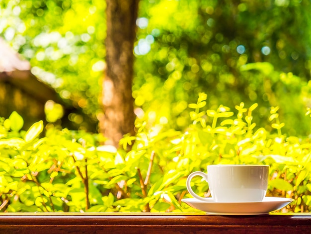 Outdoor patio with beautiful nature view and white coffee cup Free Photo