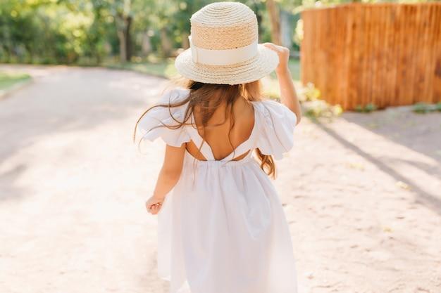 晴れた朝、通りに立っている日焼けした肌の少女の後ろからの屋外写真。魅力的な女性の子供は、公園で踊るリボンと白いドレスで飾られた麦わら帽子をかぶっています。 無料写真