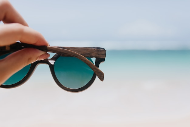 Outdoor photo of ocean with female hand on foreground. woman holding summer sunglasses on sea. Free Photo