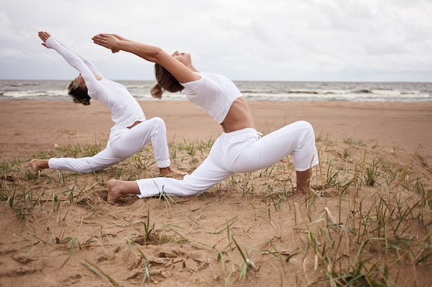 Outdoor picture of beautiful sporty european female and her teenage athletic son practicing hatha yoga by the sea together, standing in virabhadrasana ii or warrior 2 pose on deserted sandy beach Free Photo