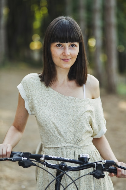 Outdoor portrait of attractive young brunette on a bicycle. Free Photo