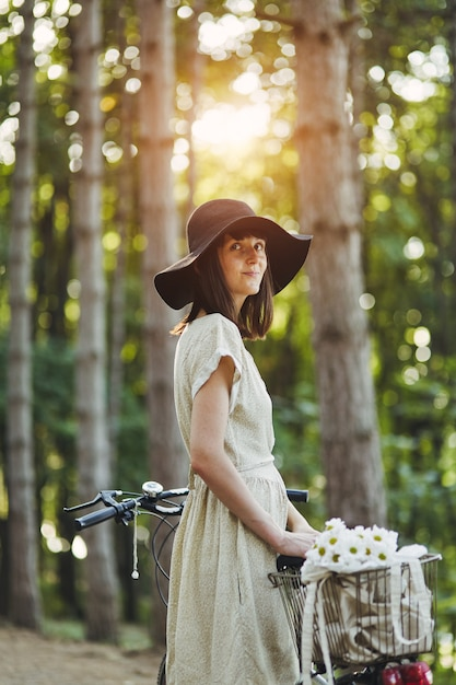 Outdoor portrait of attractive young brunette in a hat on a bicycle. Free Photo
