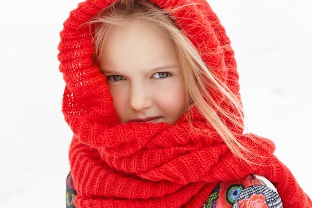 Ritratto all'aperto di bella bambina caucasica bionda avvolta in sciarpa rossa calda Foto Gratuite