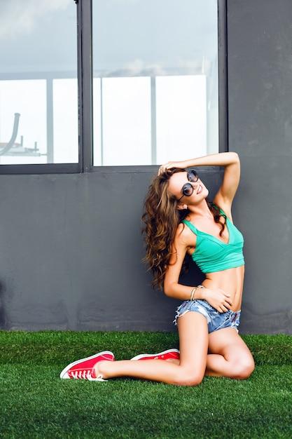 Ritratto all'aperto di una bellissima modella giovane con lunghi capelli morbidi sorriso scuro che ride e si diverte da solo, indossa un top luminoso, vintage e occhiali da sole. stile urbano. Foto Gratuite