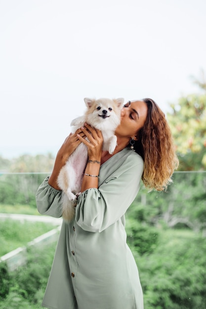 Outdoor portrait of curly european tanned woman holds happy pet dog pomeranian spitz Free Photo