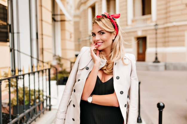 Ritratto esterno di elegante signora sorridente con nastro rosso in capelli biondi. attraente giovane donna in cappotto beige e orologio da polso alla moda in posa in mezzo alla strada e ridendo. Foto Gratuite