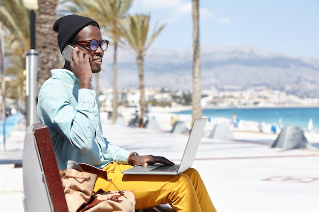 Outdoor portrait of handsome african male wearing stylish clothing and shades relaxing on bench of hotel beach during vacations in tropical country, using notebook computer and talking on mobile Free Photo