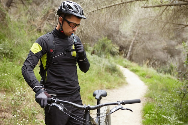 Outdoor portrait of handsome professional rider in cycling clothing holding handlebar of black motor-powered bike, drinking water out of plastic tube during small break while riding in woods Free Photo