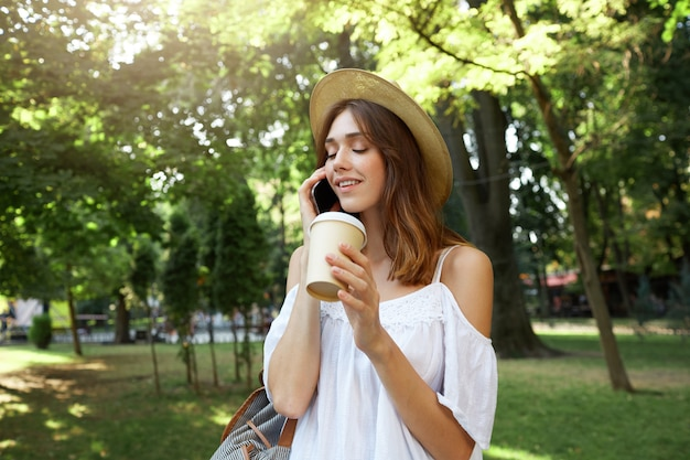 Outdoor portrait of happy cute young woman wears stylish summer hat and white dress, feels relaxed, smiling and drinking takeaway coffee on the street in city Free Photo