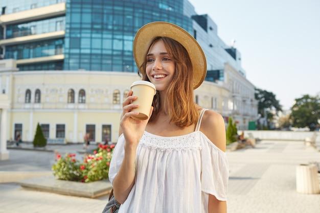 Outdoor ritratto di felice carino giovane donna indossa elegante cappello estivo e abito bianco, si sente rilassato, sorridente e bere caffè da asporto per strada in città Foto Gratuite