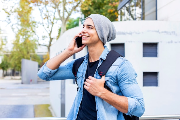 Outdoor portrait of modern young man with mobile phone in the street. Premium Photo