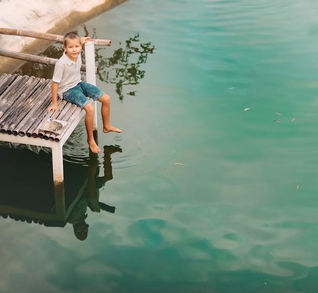 호수의 부두에 앉아 작은 귀여운 소년의 야외 초상화 프리미엄 사진