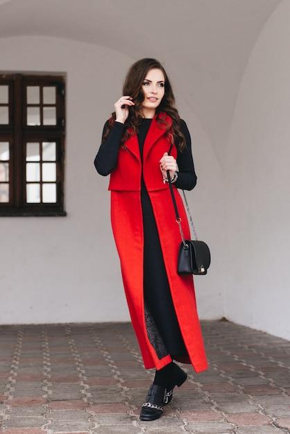 黒の服と長い赤いベストで旧市街の通りにスタイリッシュな若い女の子の屋外の肖像画。モデルがヨーロッパの都市の通りでポーズをとる Premium写真
