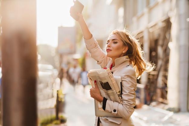 朝タクシーを待っているトレンディな服装でアクティブなビジネスウーマンの屋外のポートレート 無料写真
