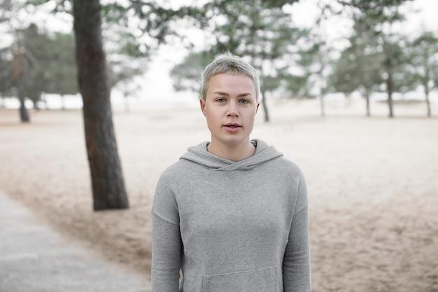 トレンディな灰色のパーカーを着て、公園で一人で走り、持久力と強さに取り組んでいる間、休息中に息をのむ魅力的なファッショナブルな金髪の短い髪の女性の屋外の肖像画 無料写真