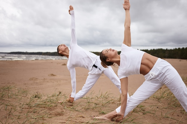 Открытый портрет привлекательной женщины и молодого мужчины со спортивными телами, одетых в белые наряды, практикующих йогу на берегу моря во время ретрита, выполняющих уттхита триконасану или позу вытянутого треугольника Бесплатные Фотографии