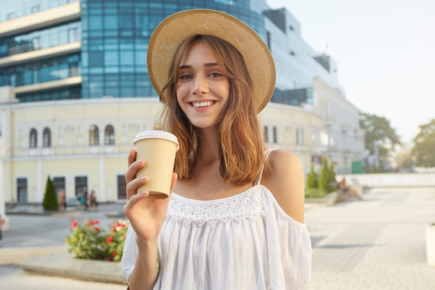 陽気な魅力的な若い女性の屋外の肖像画は、スタイリッシュな帽子をかぶって、幸せを感じ、立って、夏の街でテイクアウトコーヒーを飲みます 無料写真