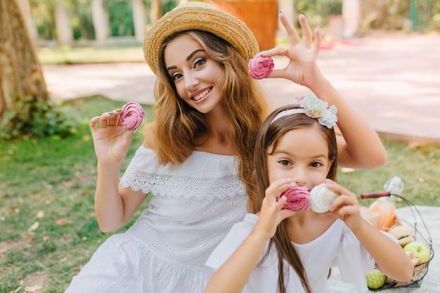 ヴィンテージのドレスを着た陽気な若い女性と自然にポーズをとって黒髪のリボンで楽しい女の子の屋外の肖像画。公園でおいしいクッキーを保持している幸せな母と娘。 無料写真