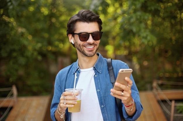 スマートフォンを手に、良いニュースを読んで、いい気分で、プラスチック製のコップでアイスティーを飲むハンサムな黒髪の男性の屋外の肖像画 無料写真