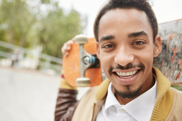 Открытый портрет красивого мужчины с темными глазами, бородой и усами, держит скейтборд за головой Бесплатные Фотографии
